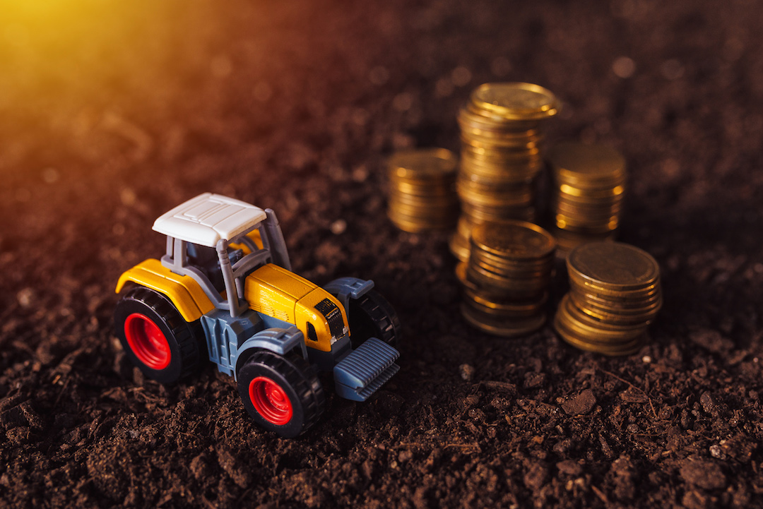 Small toy tractor sitting next to coins featured image for 7 mistakes to avoid when applying for a machinery loan blog.
