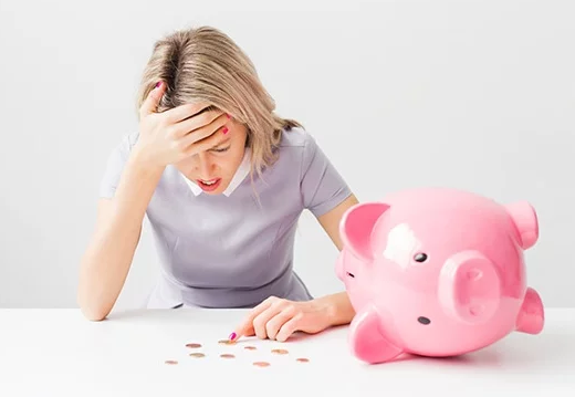 Woman Counting Coins in Front of a Piggy Bank